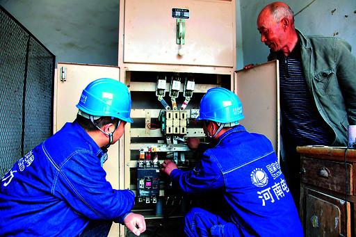 3月30日,供电人员在浚县30万亩高标准粮田示范片的配电房检修电路.